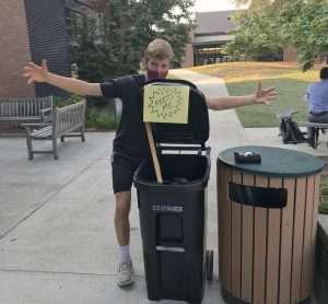 """Student wrapping arms around """"Feed me"""" sign on bin"""