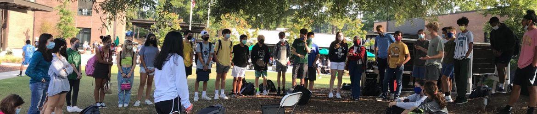 Students in outdoor meeting under tree